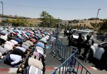 Palestinian Muslims pray outside of Jerusalem´s old city while Israeli police stand guard.