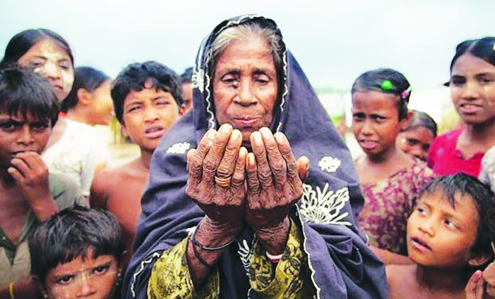 Rohingya Muslim woman prays for relief from oppression as children look on.
