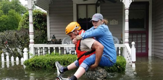 A Texas National Guardsman carries a resident from her flooded home following Hurricane Harvey in Houston