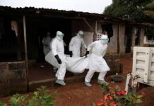Aid workers remove ebola corpse from the home.